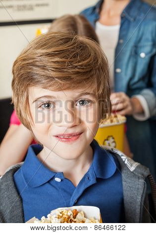 Portrait of cute boy at cinema with family standing in background