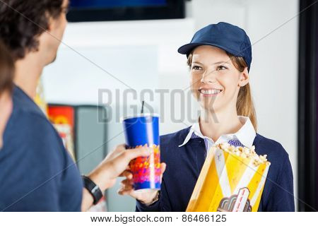 Happy female worker selling popcorn and cold drink to man at cinema