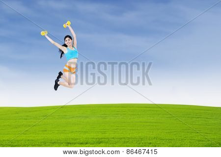 Woman Lifting Dumbbell Outdoor