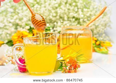 golden honey pouring from wooden stick