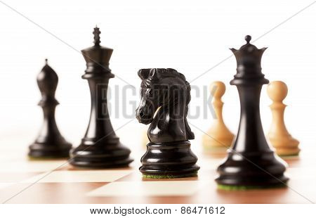 Black chess pieces with white pawns in the background on a chessboard