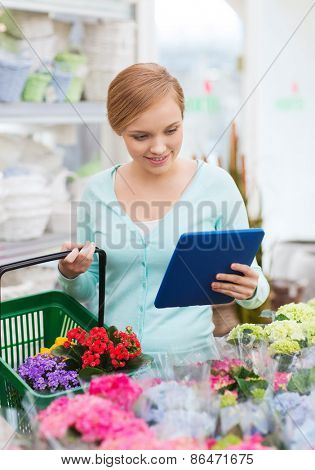 people, gardening, shopping, sale and consumerism concept - happy woman with tablet pc computer and basket choosing and buying flowers at flower shop