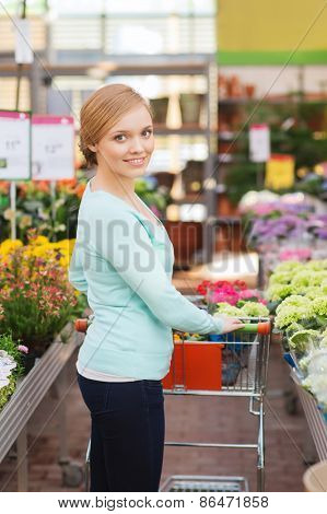 people, gardening, shopping, sale and consumerism concept - happy woman with trolley buying flowers at greenhouse or shop