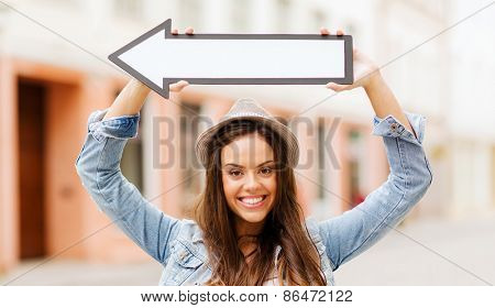 holidays and tourism concept - beautiful girl showing direction with arrow in the city