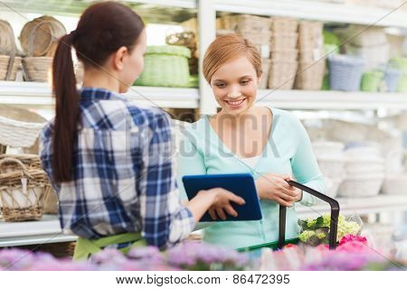 people, gardening, shopping, sale and consumerism concept - happy gardener with tablet pc helping woman with choosing flowers at flower shop