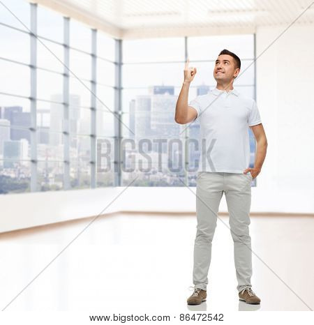 real estate, sale, business, gesture and people concept - smiling man pointing finger up over empty apartment or office room with big window and city view background