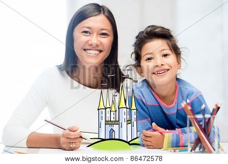 people, family, childhood, creativity and leisure concept - happy mother and daughter drawing fairytale castle at home