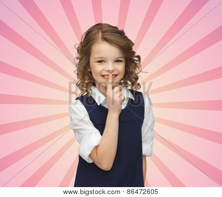 people, children, secrecy and mystery concept - happy girl showing hush gesture over pink burst rays background