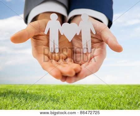 people, homosexuality, same-sex marriage and love concept - close up of happy male gay couple holding paper cutout love symbol over blue sky and grass background