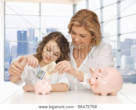 people, family, finances and savings concept - happy mother and little daughter putting money to piggy banks