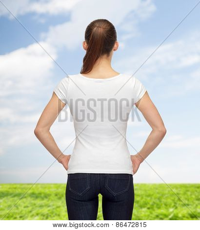 t-shirt design, advertisement and people concept - woman in blank white t-shirt from back over blue sky and grass background