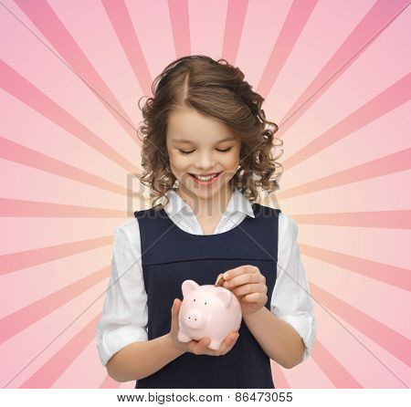 people, money, finances and savings concept - happy girl holding piggy bank putting coin over pink burst rays background