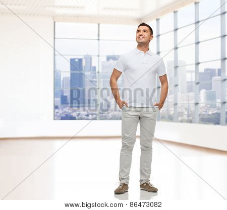real estate, sale, business and people concept - smiling man with hands in pockets looking up over empty apartment or office room with big window and city view background