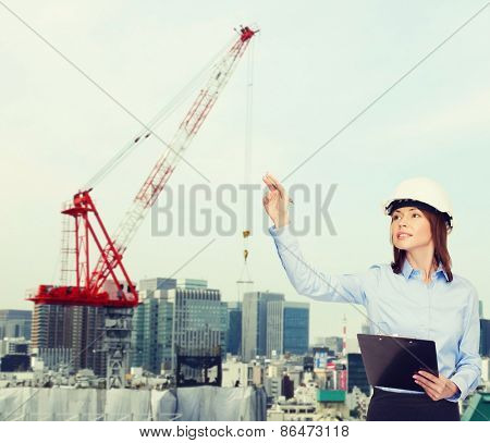 building, developing, construction and architecture concept - smiling businesswoman in white helmet with clipboard pointing finger