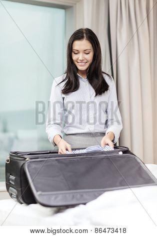 business, technology, internet and hotel concept - happy businesswoman packing things in suitcase in hotel room