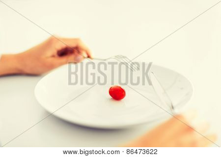 sport, healthcare and diet concept - woman with plate and one tomato