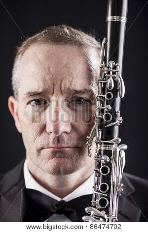 Vertical portrait of man in tuxedo holding clarinet over black background