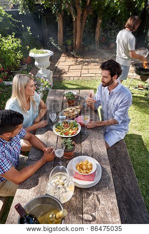 group of friends having outdoor garden barbecue dinner party