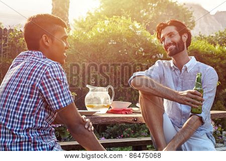group of friends having outdoor garden dinner party with beer drinks
