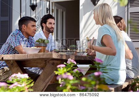 group of friends having outdoor garden dinner party