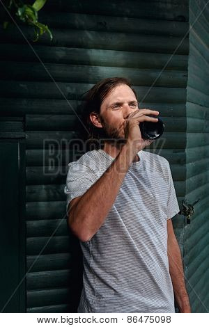 man drinking beer outdoor garden shed