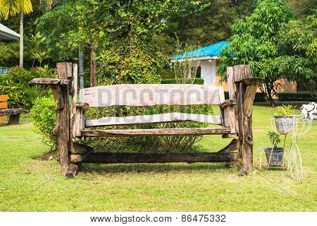 Garden wooden bench isolated in the green meadows