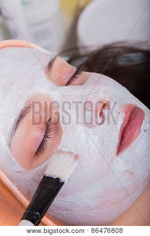 Young woman at spa procedures applying mask.