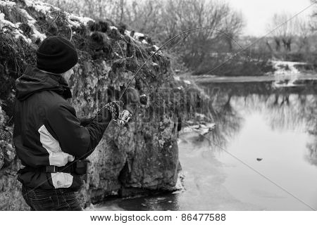 Young fisherman catches winter spinning.