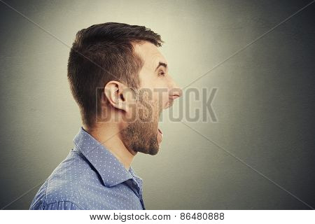 sideview of screaming man over dark background