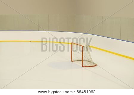 Empty hockey goal on ice rink.