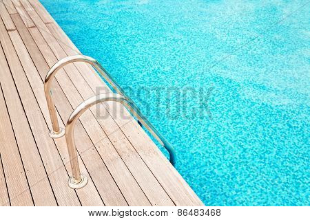 Blue Swimming Pool With Metal Hand-rails  And Wooden Decking