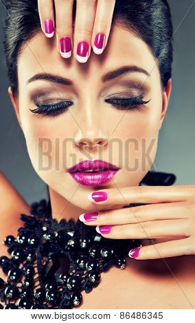 Model with fashionable nail Polish fuchsia and black necklace