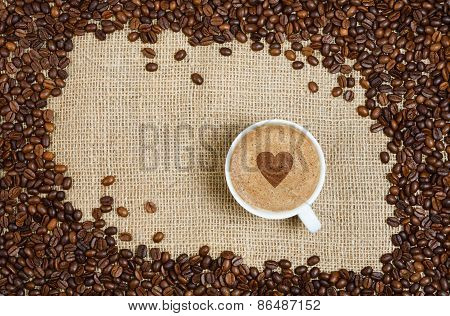 Coffee Cup And Beans On Sacking Background