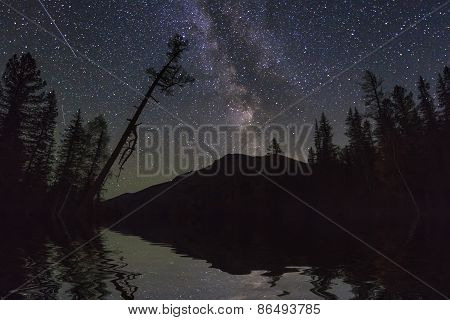 Amazing Night Landscape With Mountains And Stars. Reflection Of The Night Sky In The Lake.