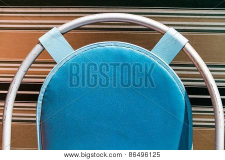 A blue coloured cushion on a metal curved frame with a background with coloured lines