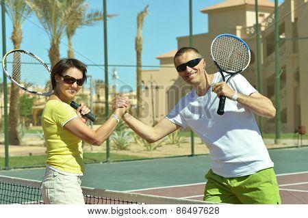 Tennis players standing near net