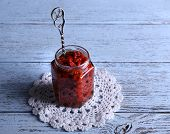 stock photo of doilies  - Jar of goji berry jam on lace doily on wooden background - JPG