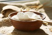 foto of spooning  - Bowl of flour with wooden spoon on burlap cloth background - JPG