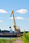 stock photo of barge  - Loading sand with the help of a yellow crane on a barge - JPG