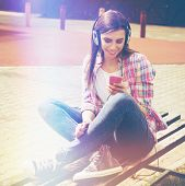 picture of sitting a bench  - Closeup outdoors portrait of millennial teenage girl with smart phone and headphones in park on sunny summer day - JPG