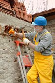 stock photo of chisel  - Construction worker demolishing old brick wall with chisel tool and hammer - JPG