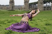stock photo of aqueduct  - purple belly dancer under the Roman aqueduct - JPG
