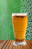 image of ice crystal  - Frost beer glass against of ice crystals and drips green background - JPG