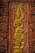 image of goddess  - Wooden goddess carving on laterite wall of Buddhist temple - JPG