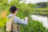 foto of catch fish  - Fisherman on the river bank in sunglasses - JPG