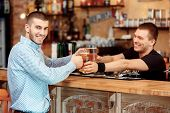 image of bartender  - Quench your thirst. Handsome young male bartender stretching out glasses with beer and smiling while standing at the bar counter