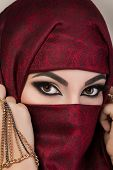 picture of niqab  - Portrait of beautiful arabian girl hiding her face behind red niqab with paisley ornament - JPG