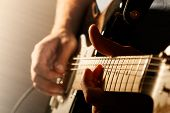 pic of low-necked  - Hands of man playing electric guitar. Bend technique. Low key photo.