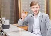 stock photo of mans-best-friend  - Cheers to all friends. Young smiling man toasting a glass of whiskey sitting at a counter of the bar ** Note: Soft Focus at 100%, best at smaller sizes - JPG