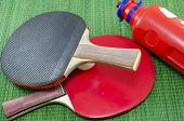 stock photo of ping pong  - Two vintage table tennis rackets and two ping pong balls on a green background - JPG